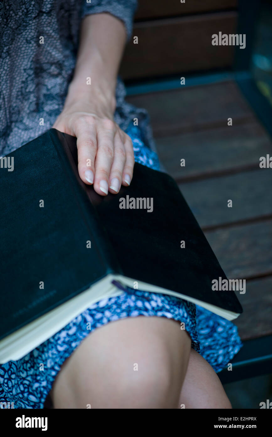 Woman sitting with open book on lap, cropped - Stock Image