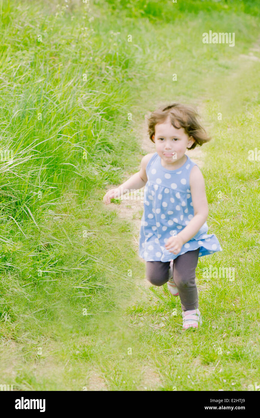 Little girl running on path through countryside - Stock Image