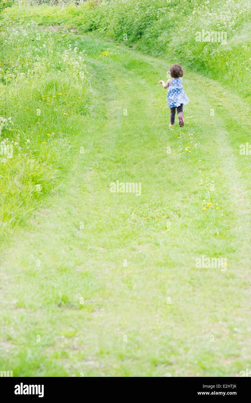 Little girl running on country path, rear view - Stock Image
