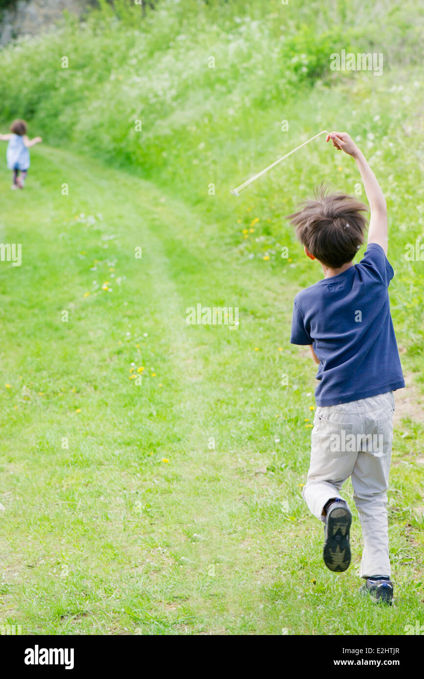Boy running on country path, rear view Stock Photo