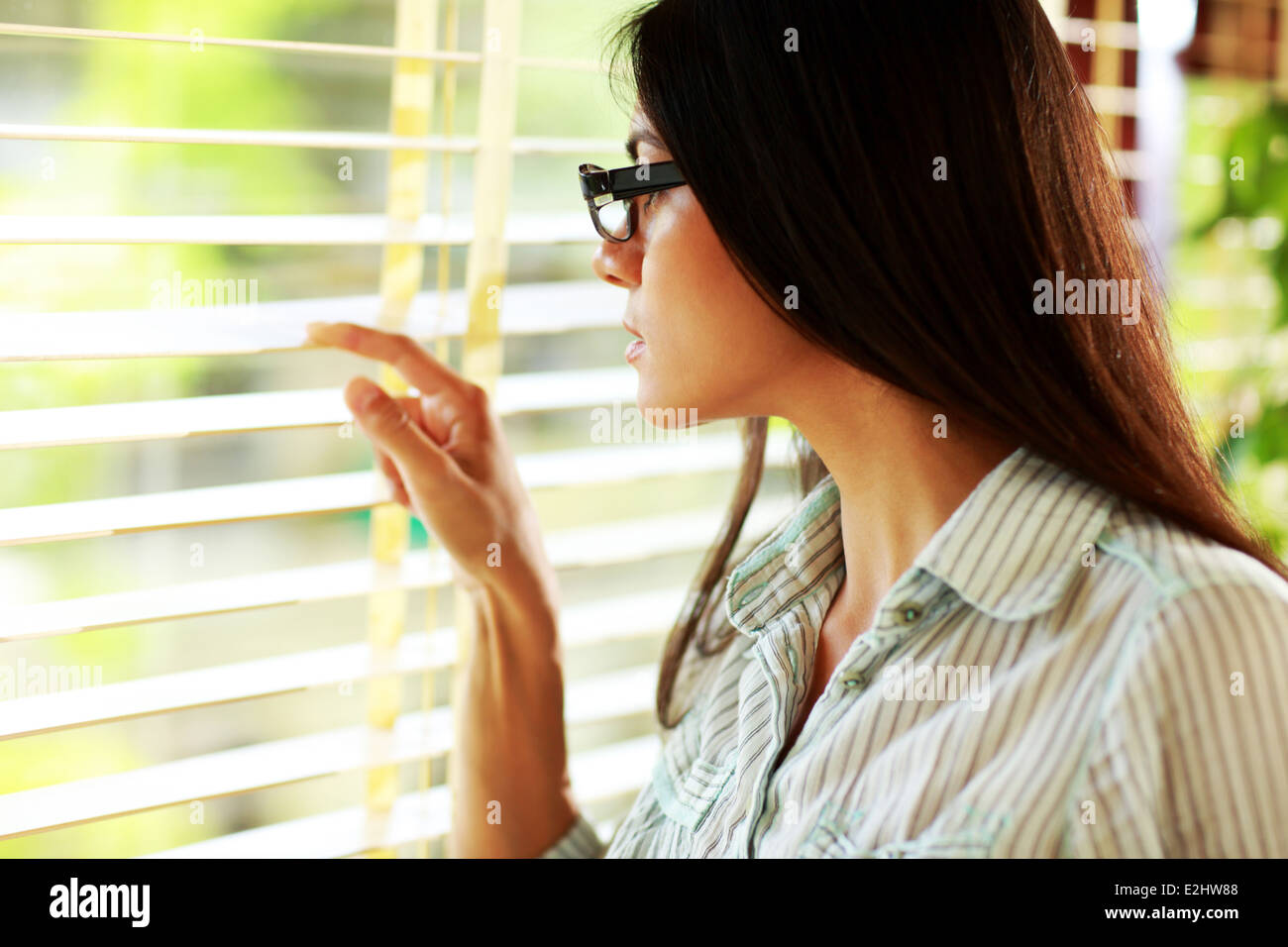 Businesswoman in glasses looking in window at office - Stock Image