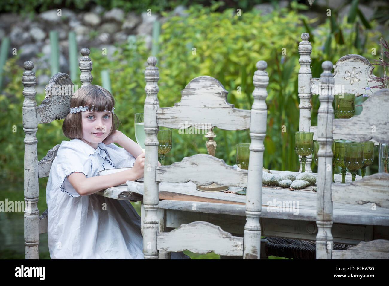 Girl sitting at dining table outdoors - Stock Image