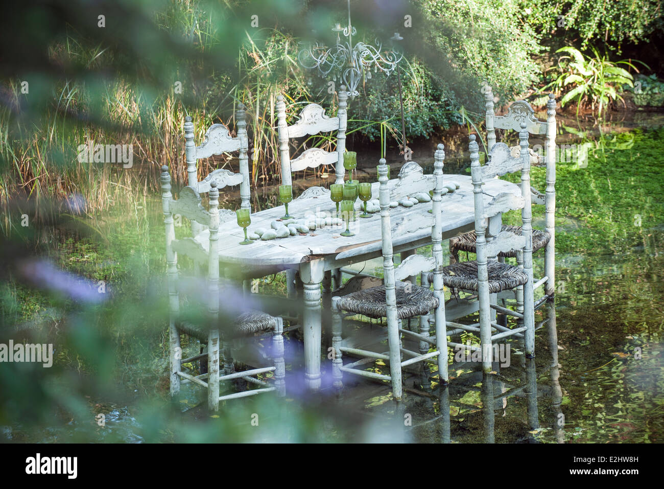 Ornate dining table floating in pond - Stock Image