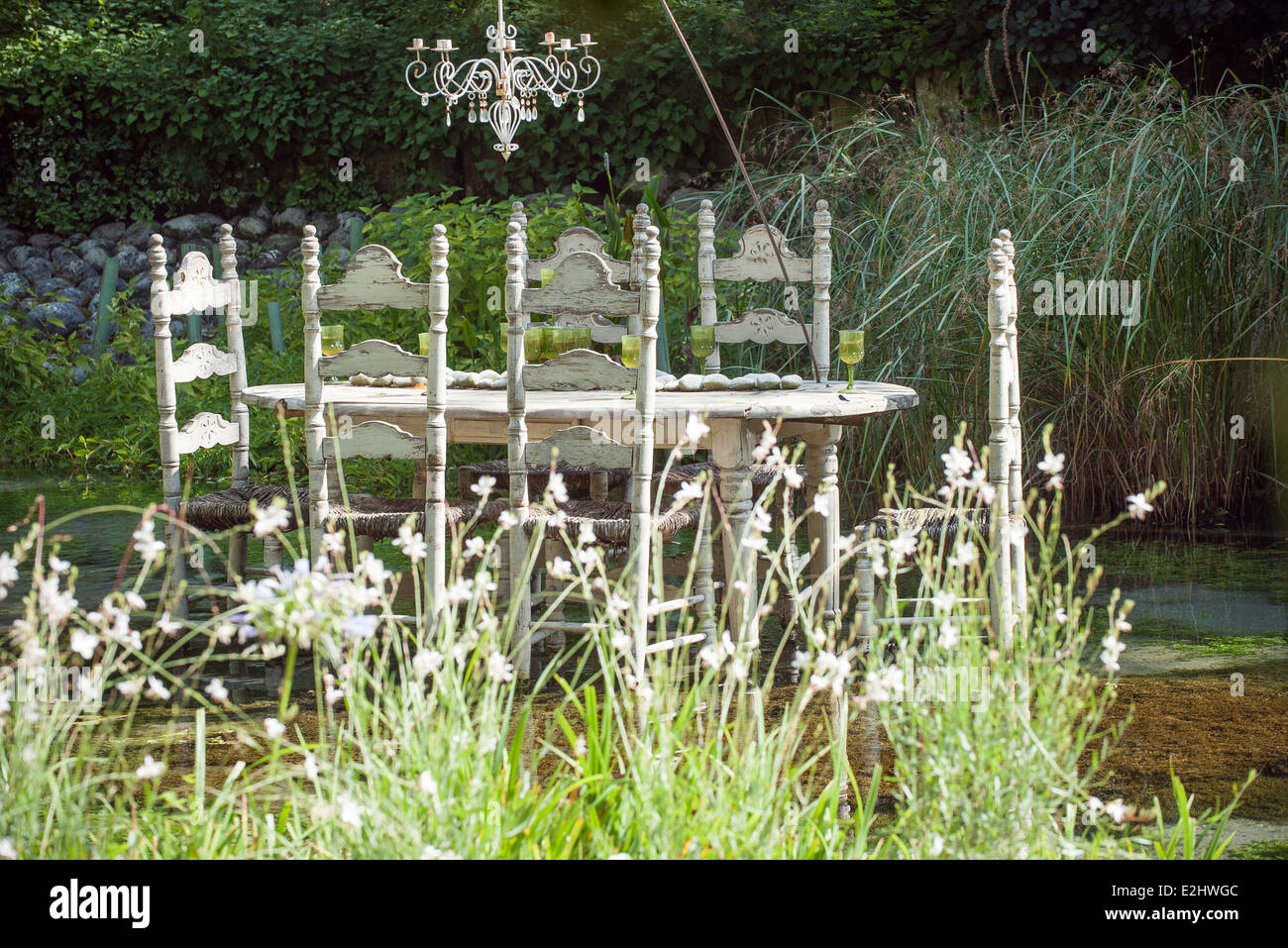 Ornate table and chairs floating on pond - Stock Image