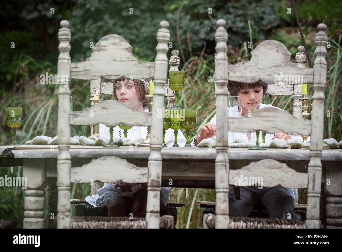 Children seated at dining room table outdoors - Stock Image
