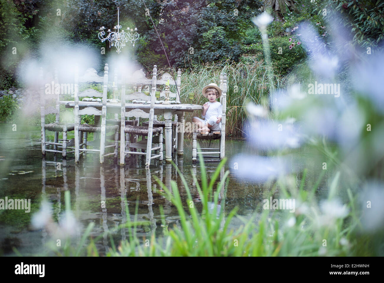 Little boy sitting at dining table floating on lake - Stock Image
