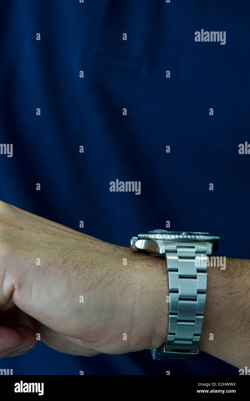 Man wearing wristwatch, checking time - Stock Image