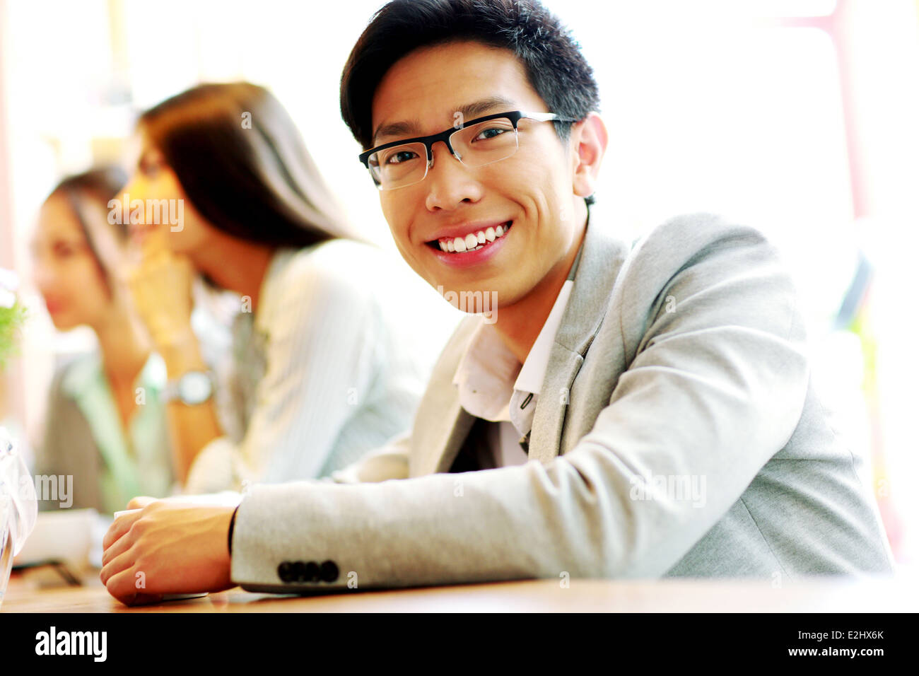 Portrait of smiling businessman sitting in front of colleagues - Stock Image