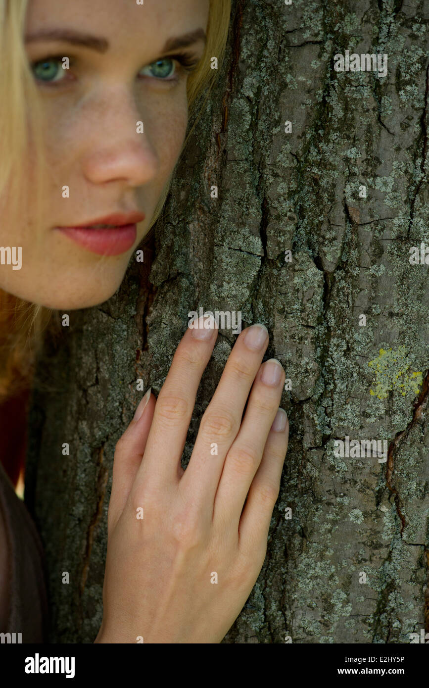 Young woman leaning against tree trunk with dreamy expression - Stock Image