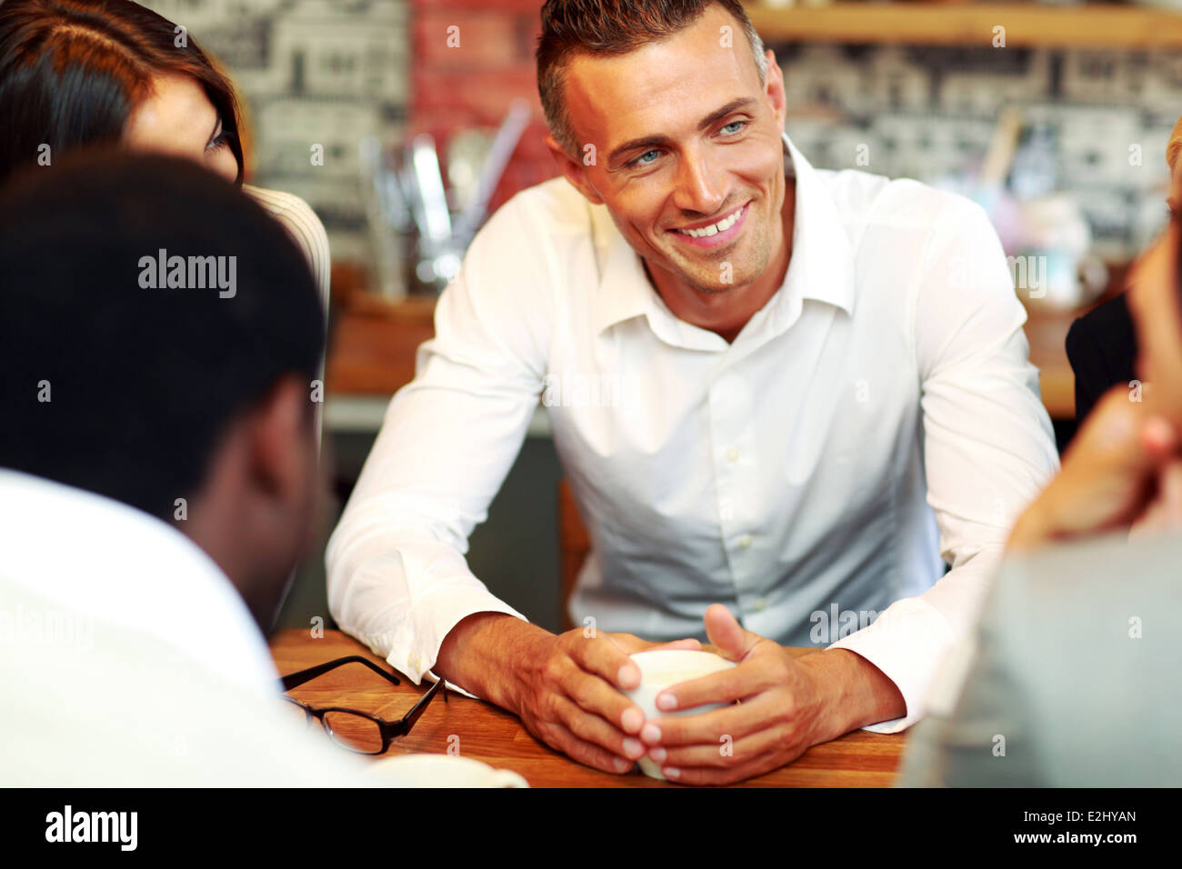 Happy business people having meeting around table in office - Stock Image