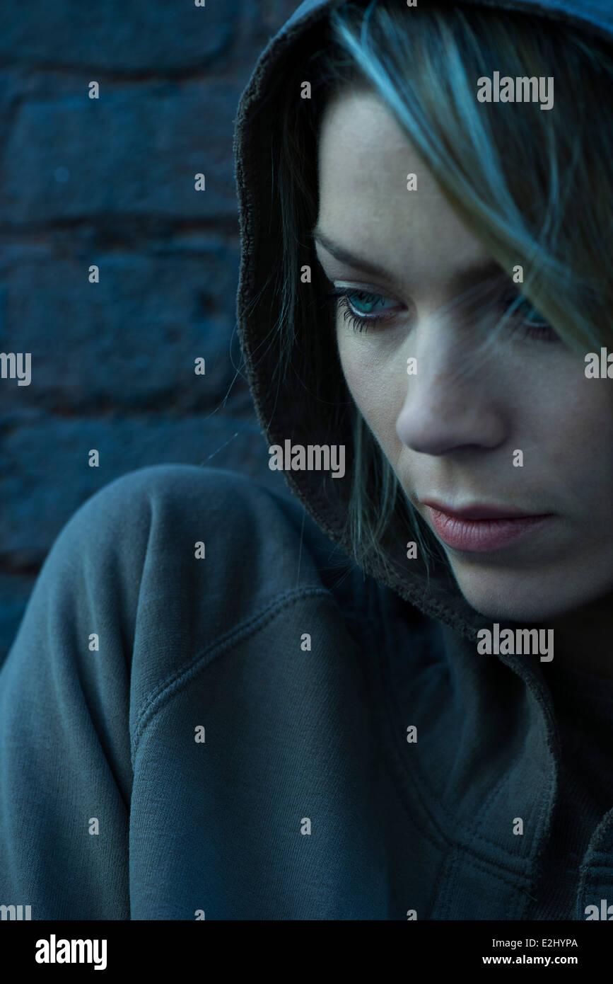 Woman in hooded sweatshirt pensively looking away - Stock Image