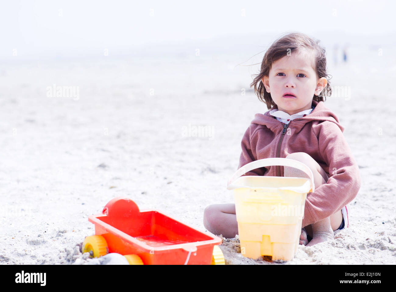 Little girl playing in sand at the beach - Stock Image