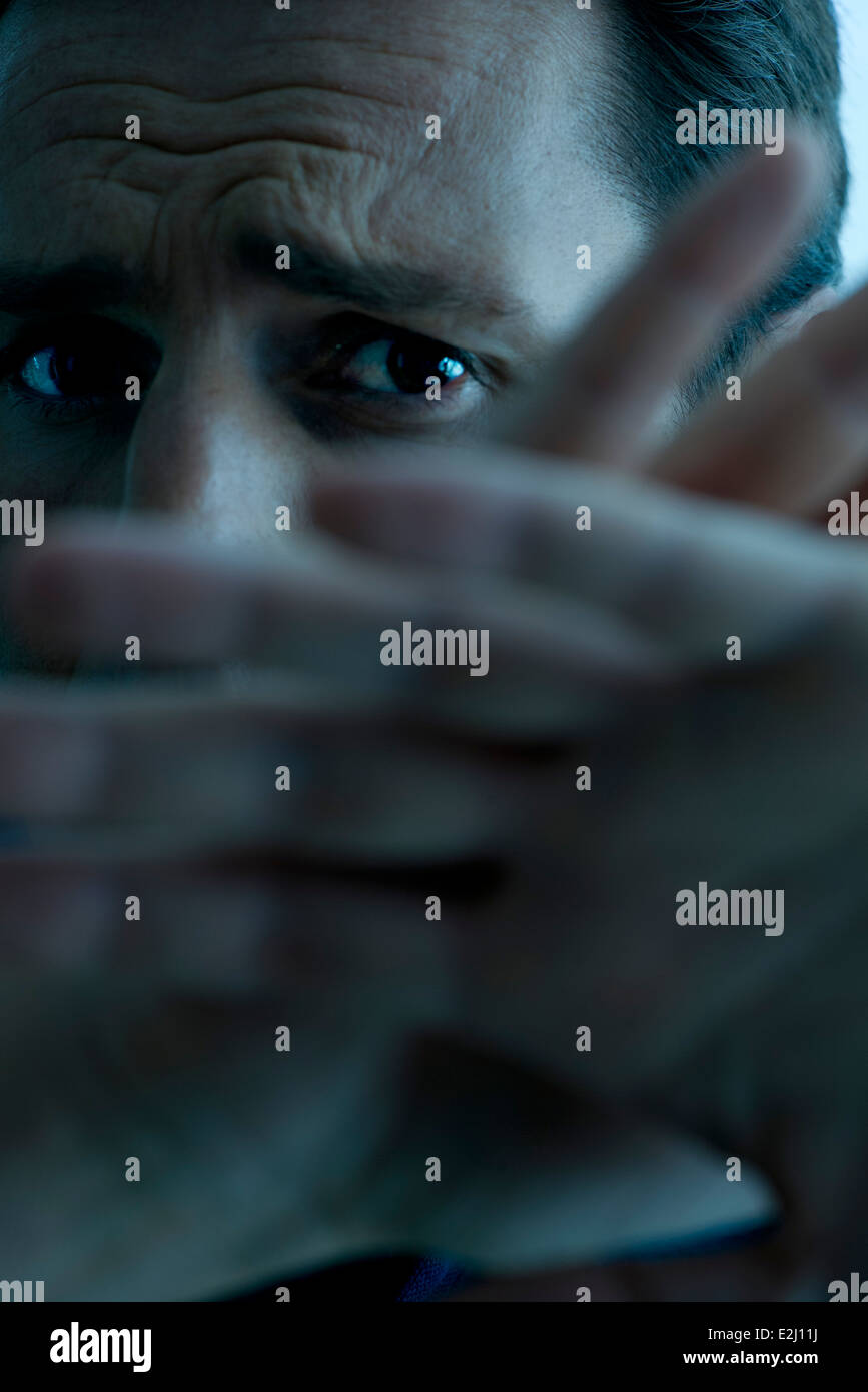 Man with hands raised warding off attack - Stock Image