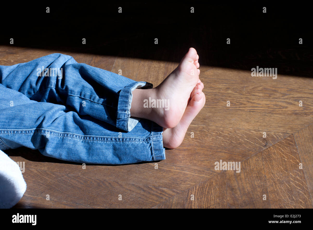 Barefoot child sitting on floor, low section - Stock Image