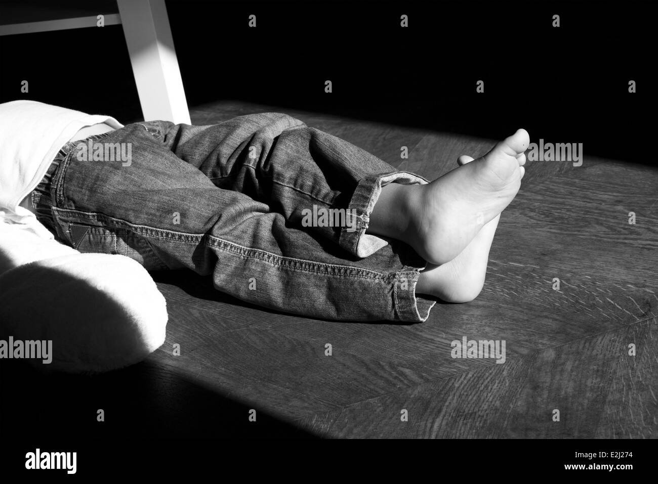 Child lying on floor with legs crossed at ankle, cropped - Stock Image
