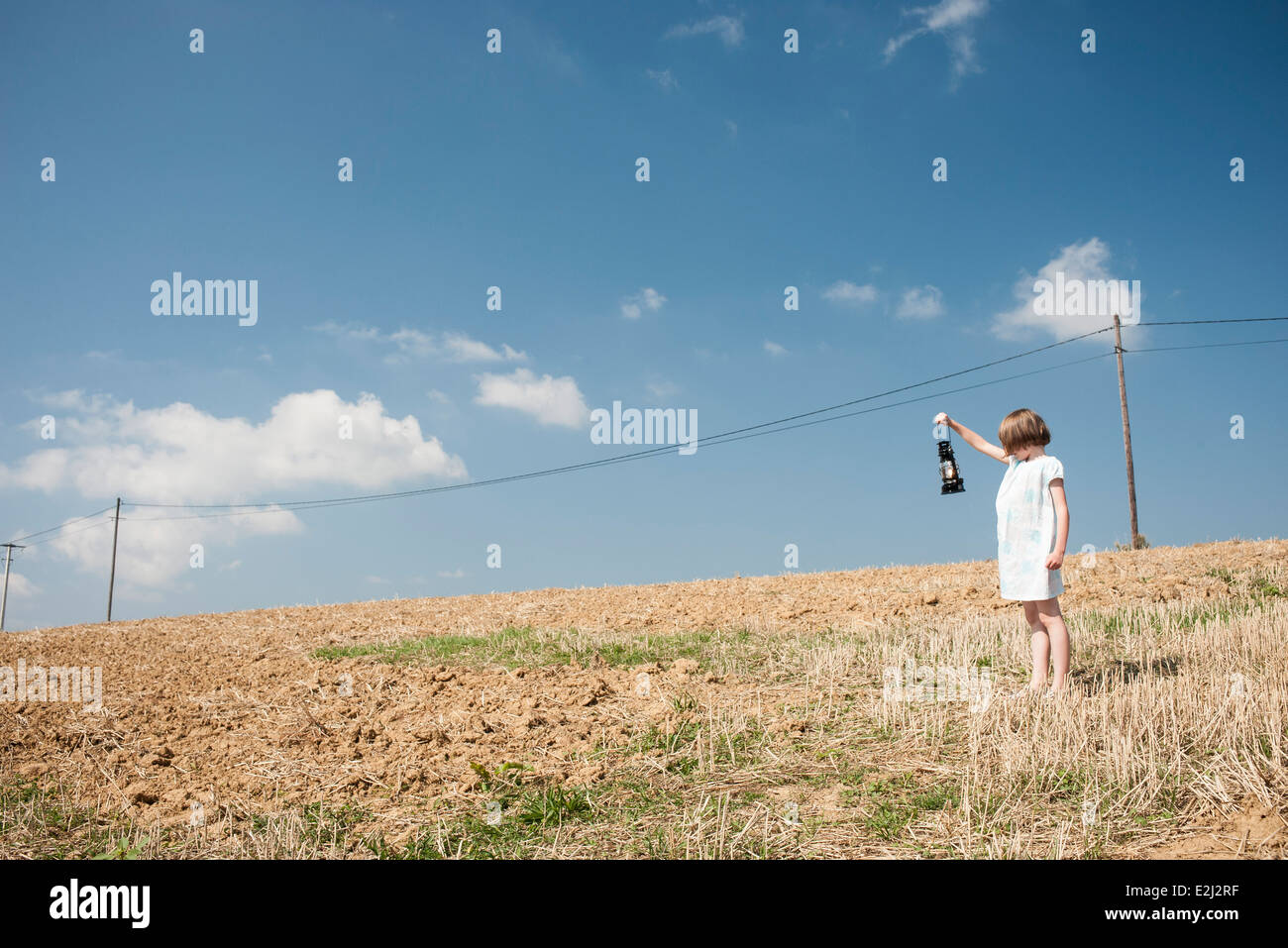Girl standing in field with old-fashioned lantern, looking at power line - Stock Image