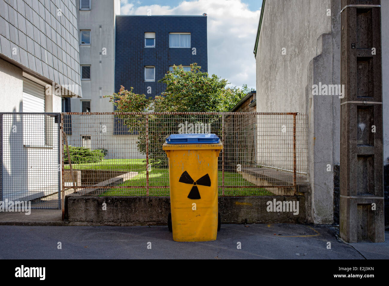 Waste receptacle with nuclear waste symbol painted on it - Stock Image