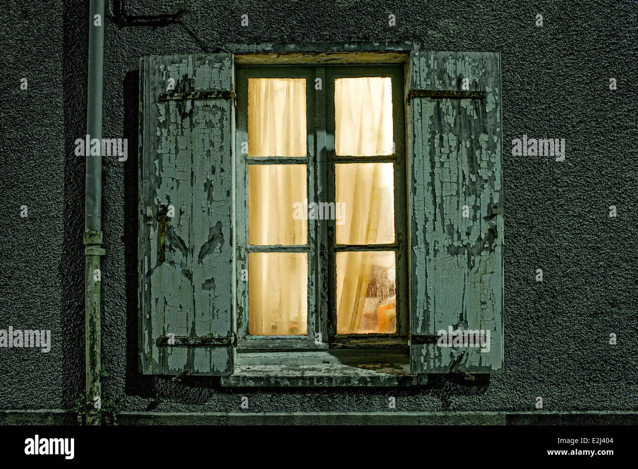 Window with dilapidated shutters illuminated at night - Stock Image