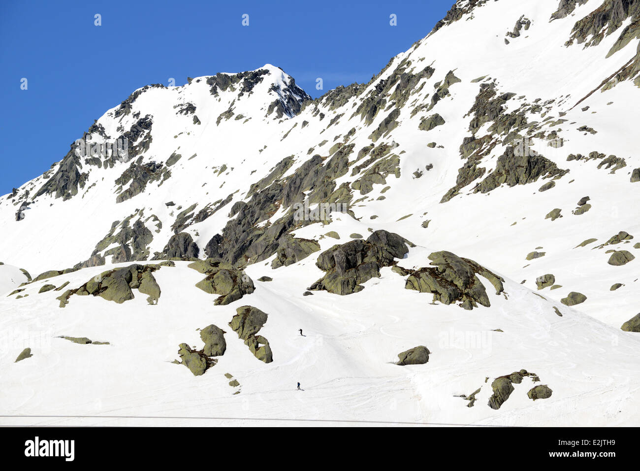 Skiiers skiing off piste on late snow in May on The Gotthard Pass or St. Gotthard Pass (Italian: Passo del San Gottardo) - Stock Image