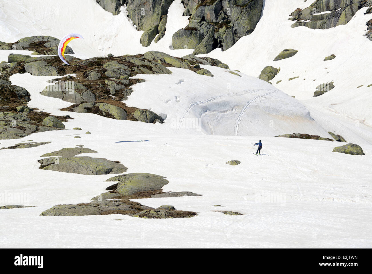 Snowkiting Skiiers skiing off piste on late snow in May on The Gotthard Pass or St. Gotthard Pass  Passo del San Stock Photo