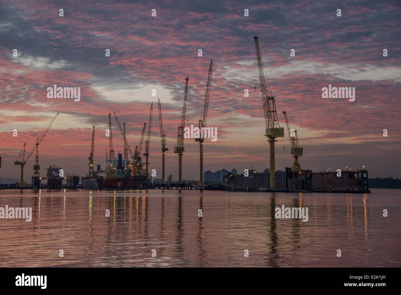 Ships at a dry dock as the sun sets in Singapore - Stock Image