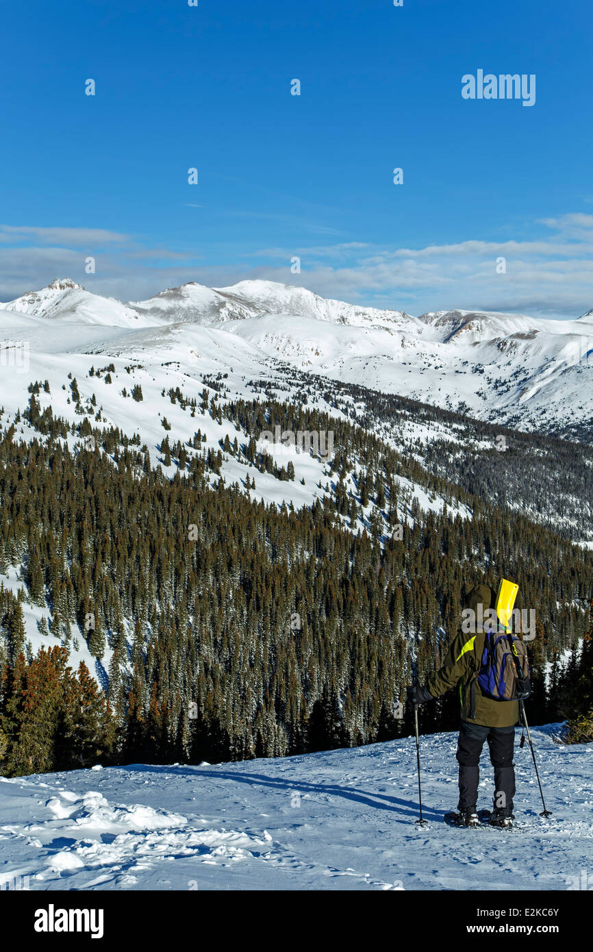 Snowshoer admiring mountain view from Loveland Pass, Colorado USA - Stock Image