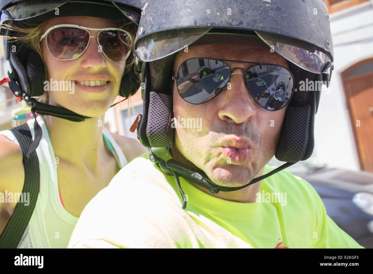 man woman couple helmet helmets sunglasses 'having fun' driving riding smiling smile kiss selfie - Stock Image