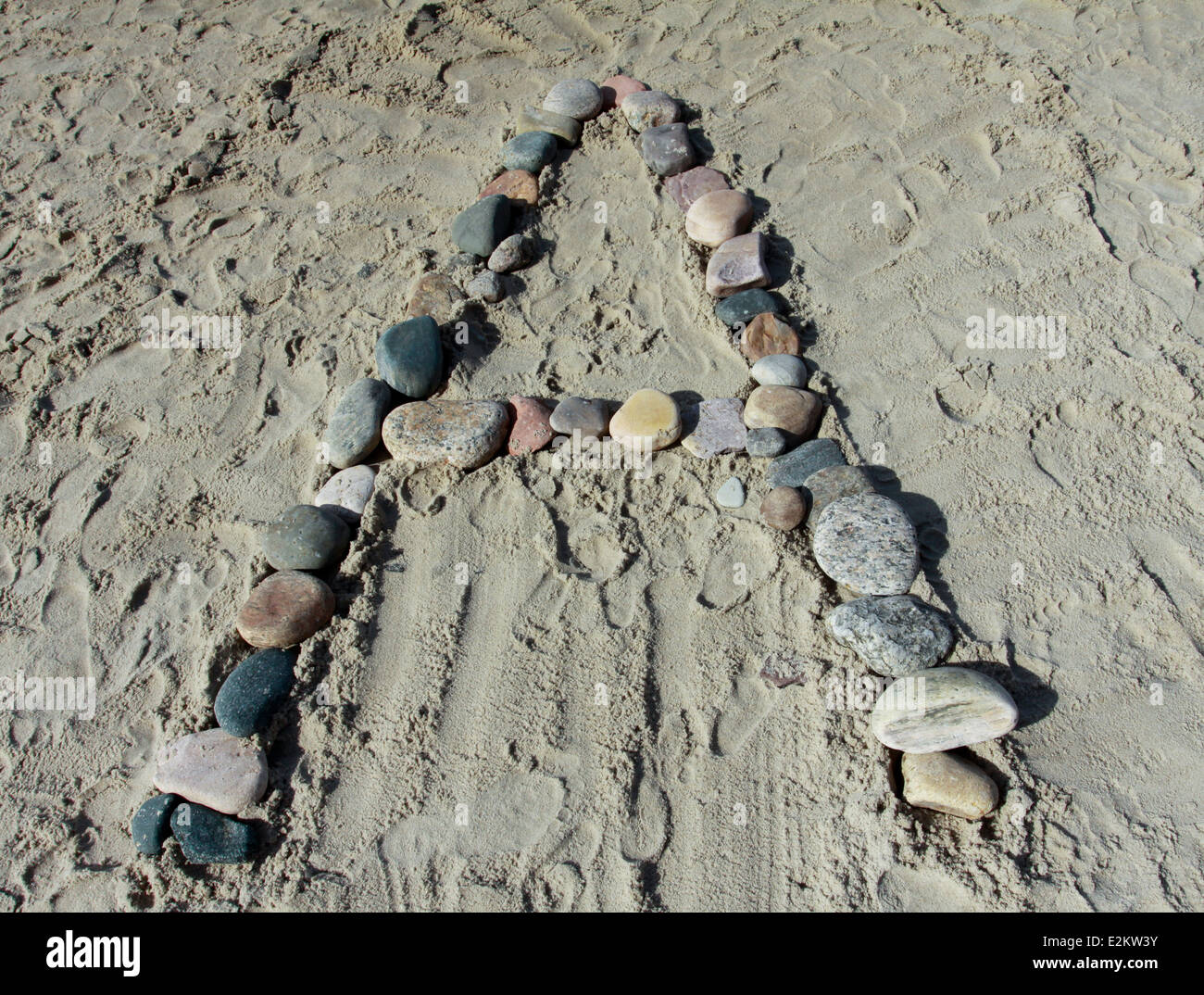 Letter A of stones on sandy beach - Stock Image