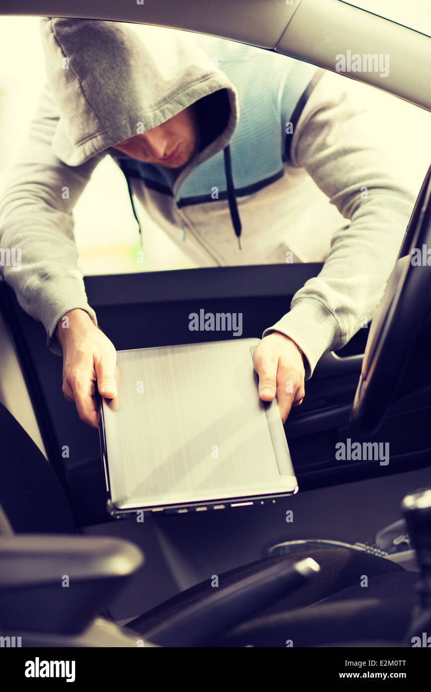 thief stealing laptop from the car - Stock Image