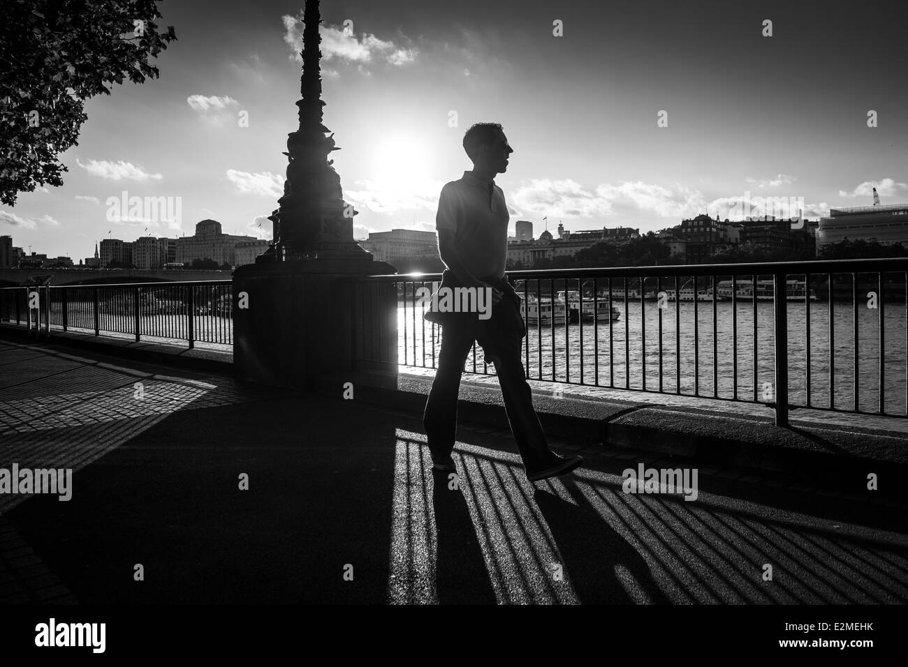 Tourist walking by the River Thames in black and white - Stock Image