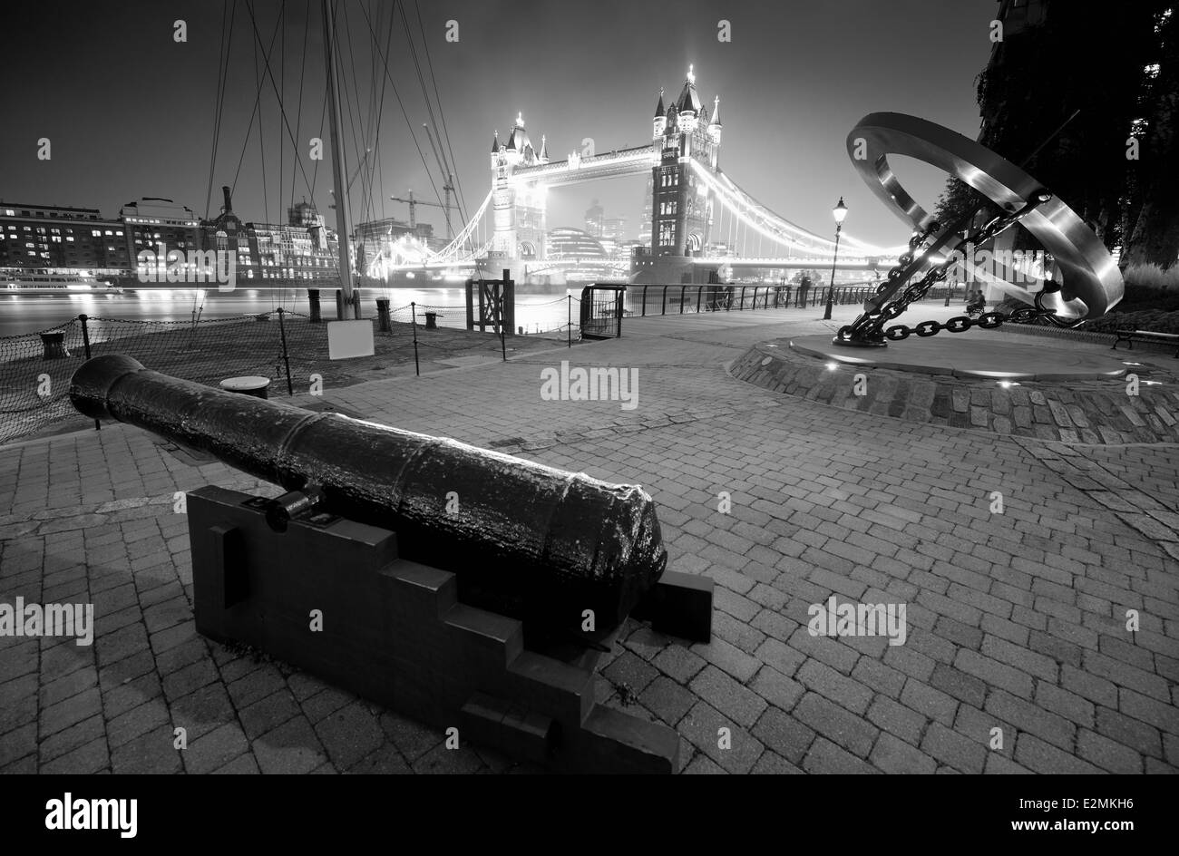 Cannon and Tower Bridge at night at St. Katherine Dock in London. - Stock Image