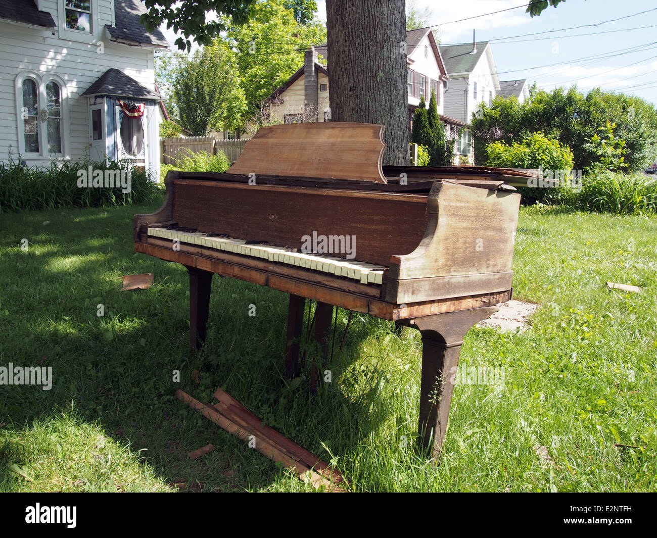 Broken old grand piano is left for trash on a front yard lawn in Woodstock, New York, USA, June 7, 2014, © - Stock Image