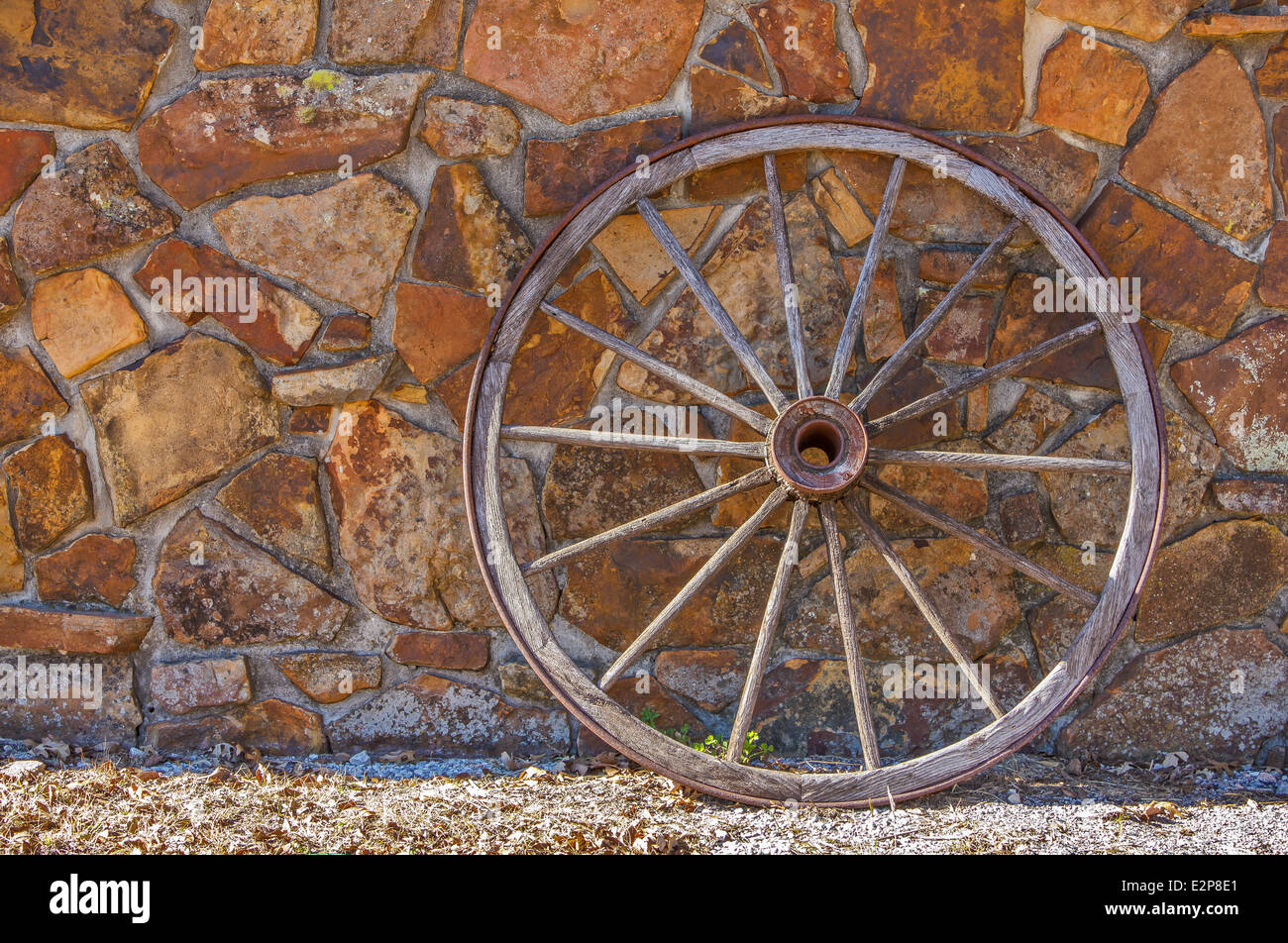 An old wagon wheel against a stone wall - Stock Image
