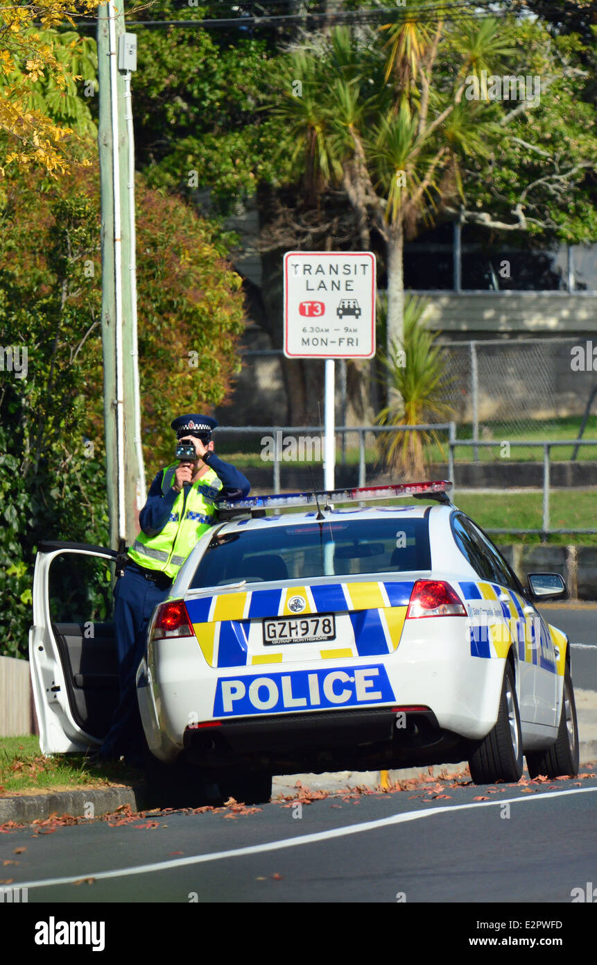 Traffic Police officer pointing his radar gun at speeding traffic. - Stock Image