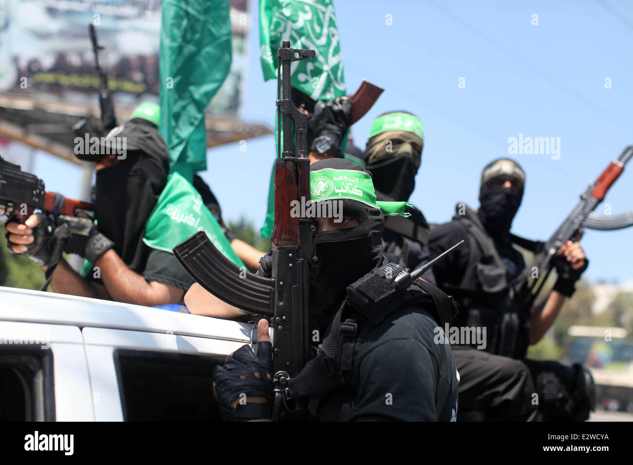 Gaza City, Gaza Strip. 21st June, 2014. Palestinian members of Hamas' armed wing surround the bodies of their - Stock Image
