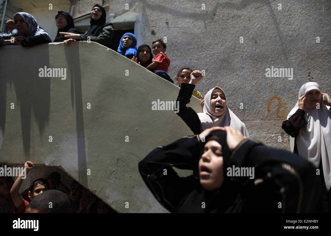 Gaza. 21st June, 2014. Relatives of a Palestinian member of Hamas' armed wing mourn during his funeral in Gaza - Stock Image