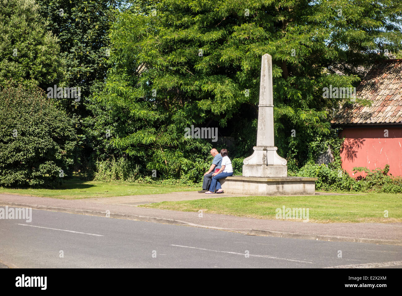 couple sat on war memorial remembering Milton - Stock Image