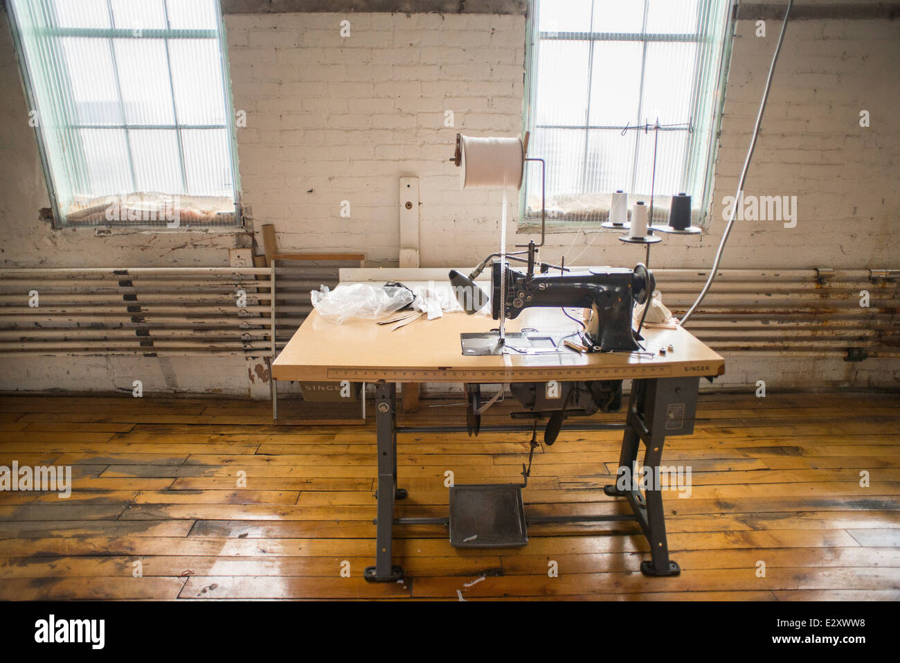 An Antique, Black Singer Sewing Machine Attached To An Antique Table With A  Foot Pedal Sits In A Corset Factory In Cortland, NY.