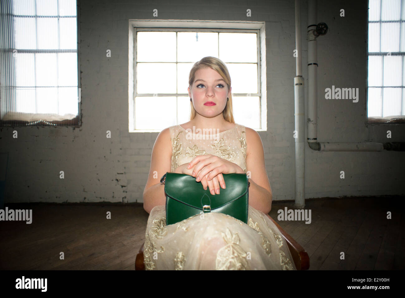 A 16-year-old Caucasian female wearing a 1960's lace dress holding a vintage green purse sits in a chair in - Stock Image