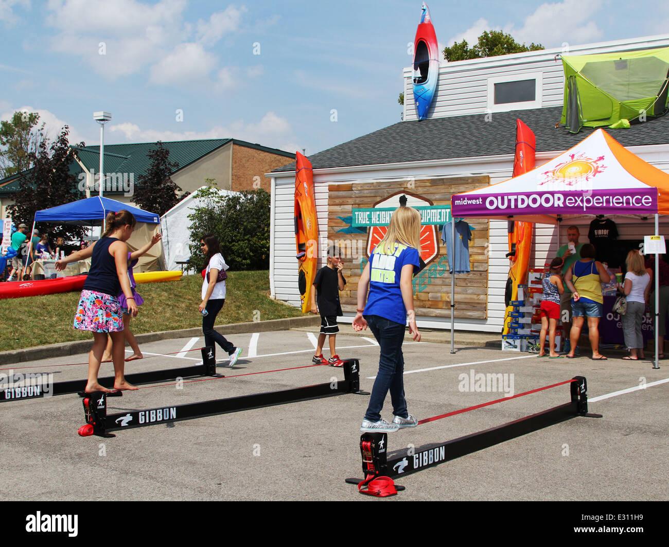 Teen girls trying a Gibbon brand Slack Line. Beavercreek Popcorn Festival, Beavercreek, Dayton, Ohio, USA. - Stock Image