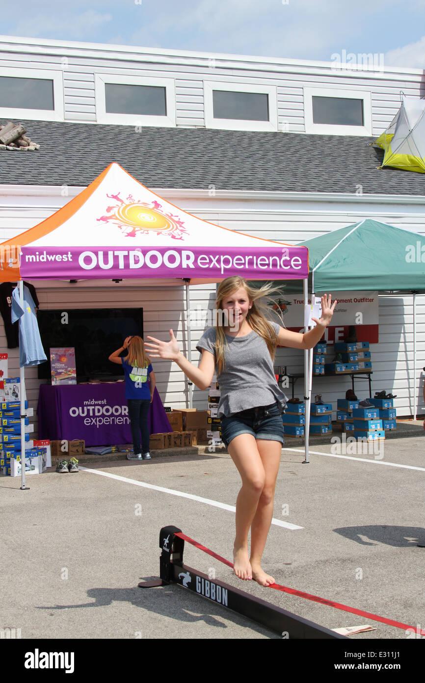 Teen girl demonstrating a Gibbon brand Slack Line. Beavercreek Popcorn Festival, Beavercreek, Dayton, Ohio, USA. - Stock Image