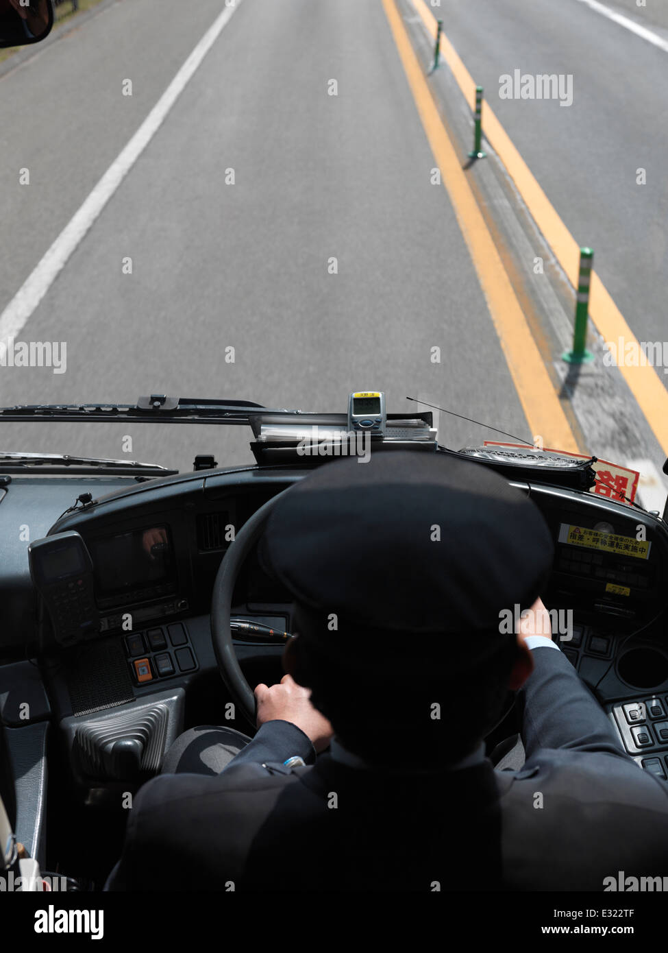 Bus driver at a steering wheel driving on a highway, high angle view. Japan. - Stock Image