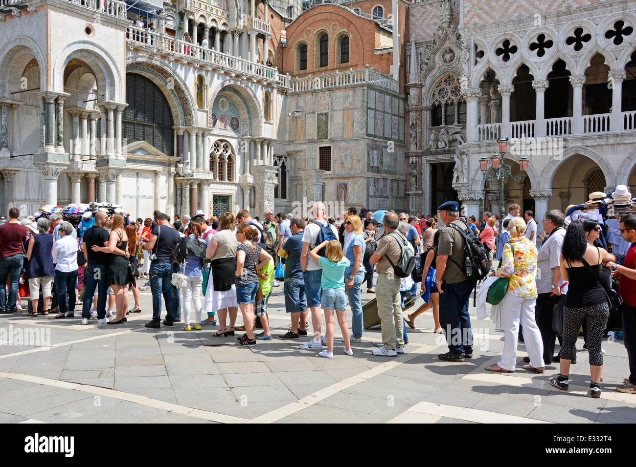 People & long queue of casually dressed summer tourists queuing waiting outside Italian Doges Palace towards historical Stock Photo