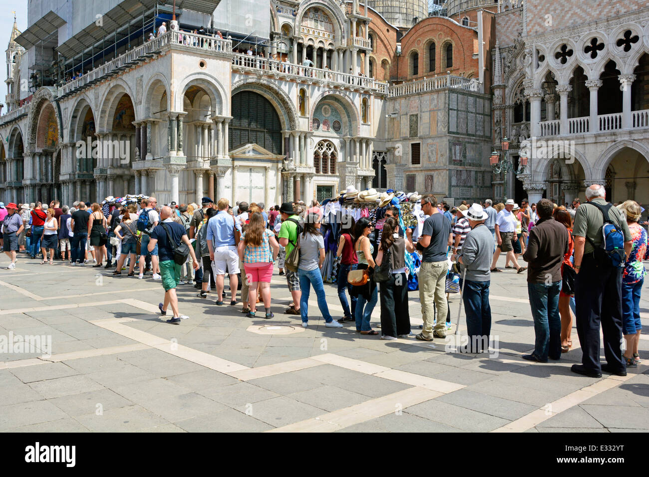 Long queue of casually dressed summer tourists people queuing & waiting outside Italian Doges Palace towards historical Stock Photo