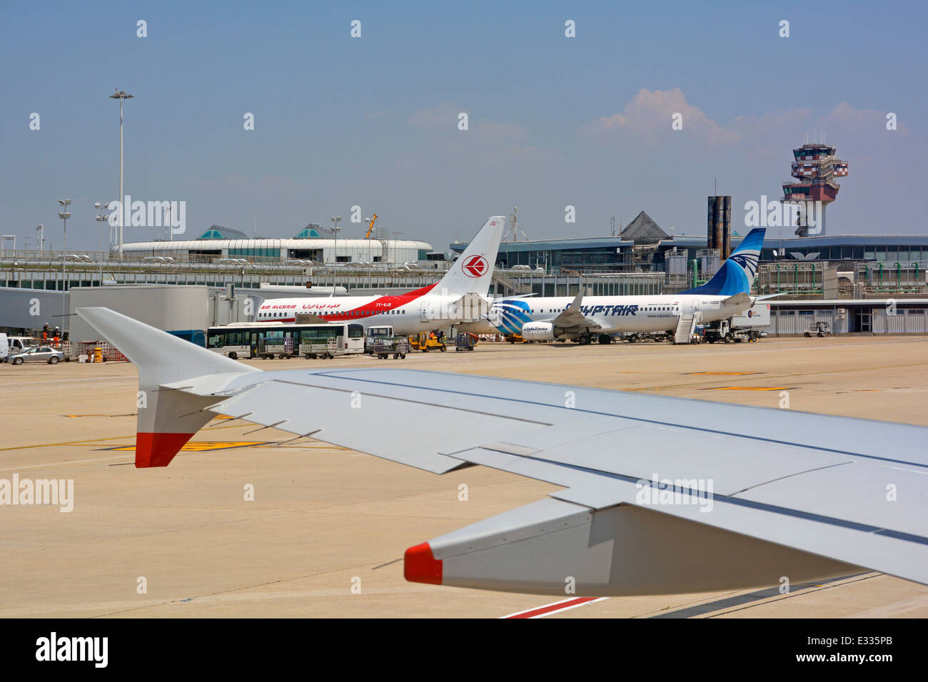 Passenger airplane taxiing out towards runway passing terminal buildings and control tower - Stock Image