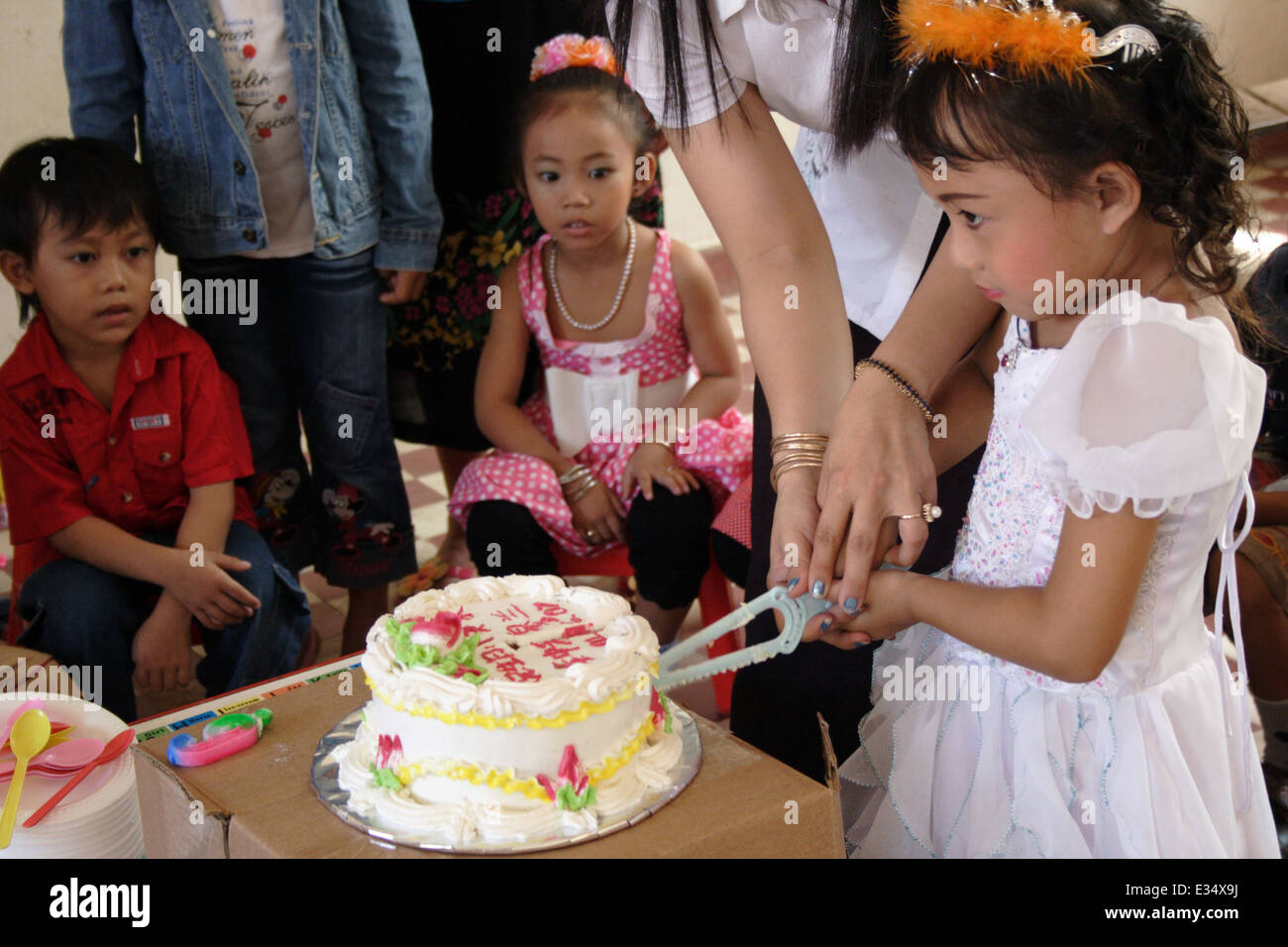 A Teacher Is Helping A 6 Year Old Asian Girl Cut Her Birthday Cake