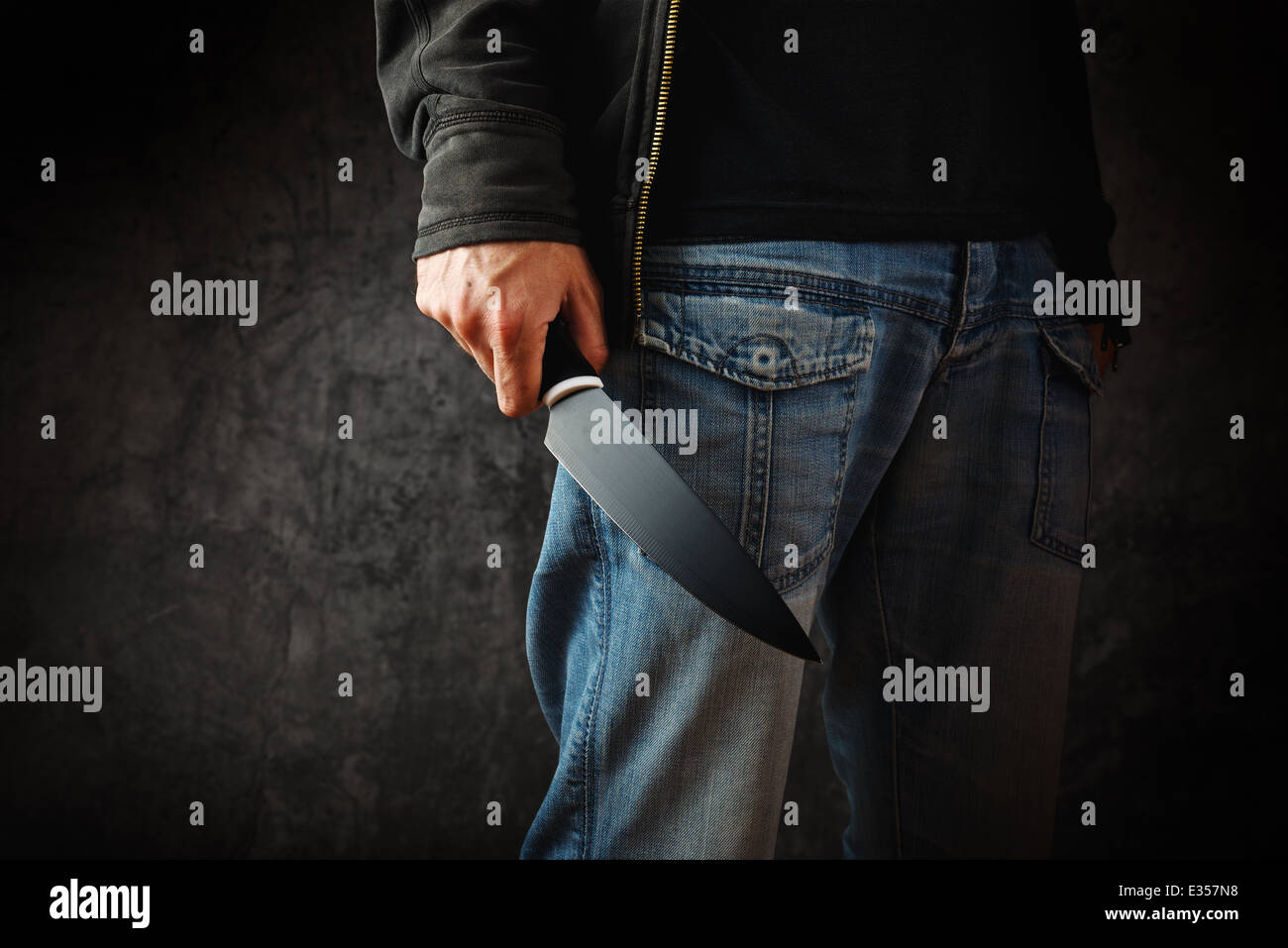 Evil man with shiny knife - a killer person with sharp knife about to commit a homicide, murder scenery. - Stock Image