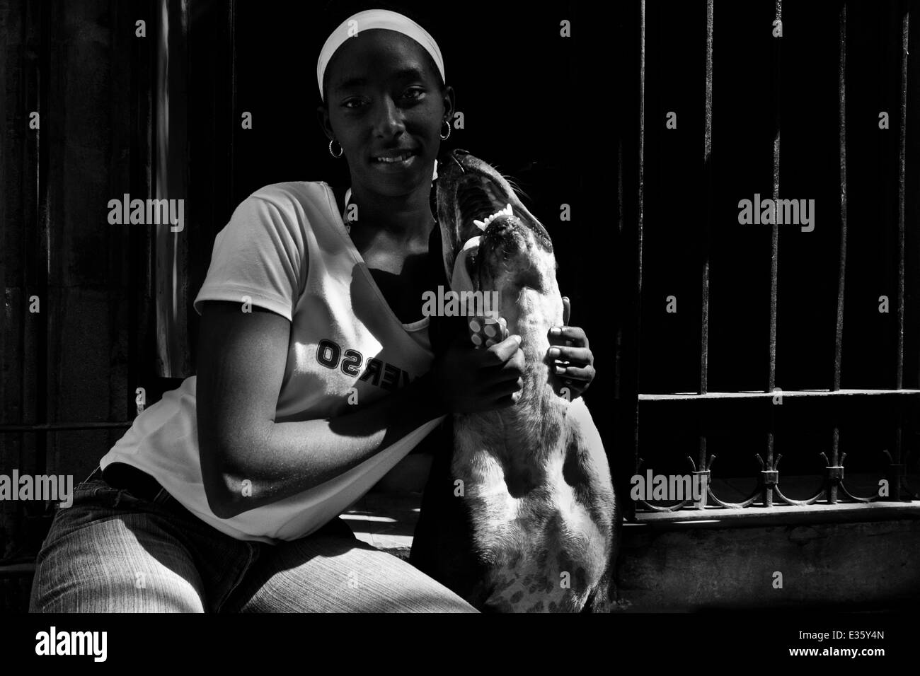 A Cuban woman poses for a picture with her amstaff dog during a sunny morning in Havana, Cuba. - Stock Image