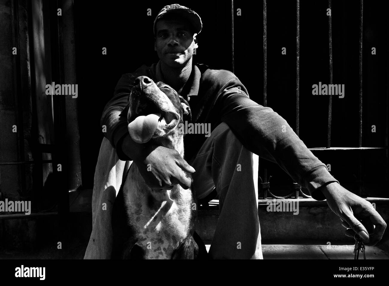 A Cuban man poses for a picture with his amstaff dog during a sunny morning in Havana, Cuba. - Stock Image
