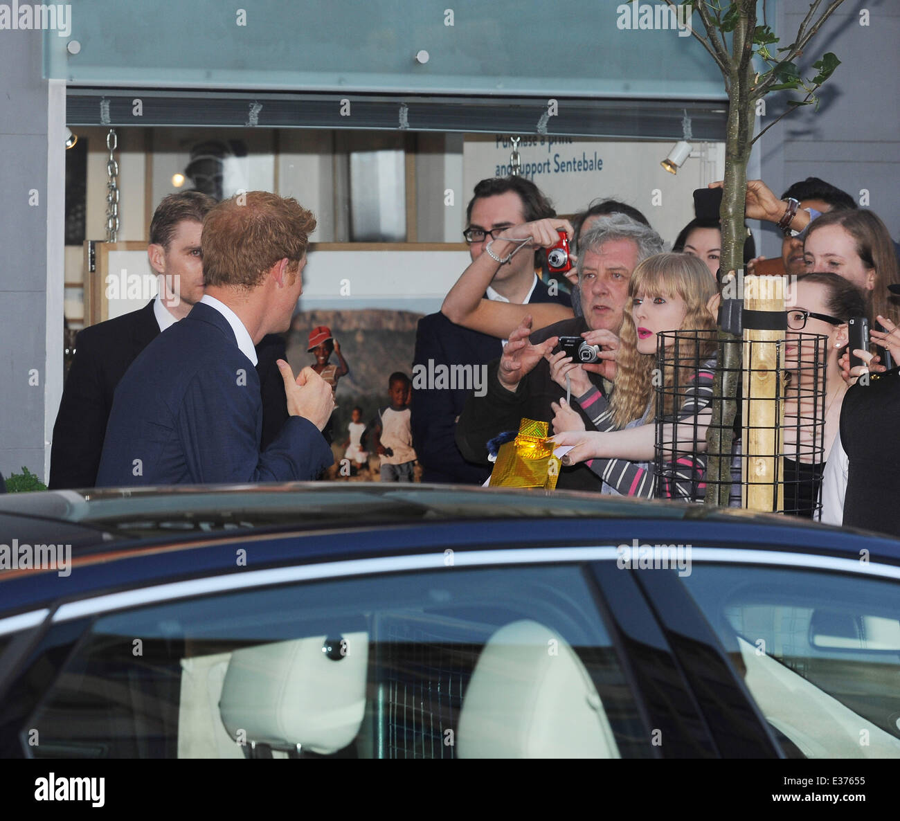 Prince Harry leaves Getty Images Gallery in London and was given a present by a fan for his new nephew Prince George. - Stock Image